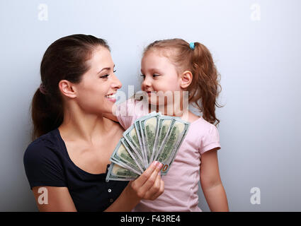 Smiling mother and happy daughter hugging, looking each other and showing dollars. Happy winning family. - Stock Photo