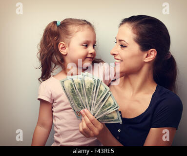 Smiling winner family hugging, looking each other and holding dollars. Happiness. Vintage closeup portrait - Stock Photo