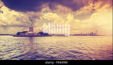 Vintage style Statue of Liberty with dramatic sunset, New York, USA. - Stock Photo