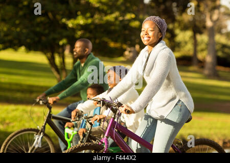 Side view of a young family doing a bike ride - Stock Photo