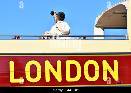 London tourist visitor photographing the sights from an open top tour bus in Trafalgar Square England UK - Stock Photo