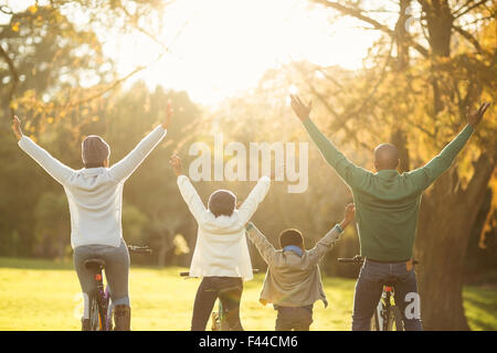 Rear view of a young family with arms raised on bike - Stock Photo