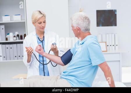 Doctor checking senior mans blood pressure - Stock Photo