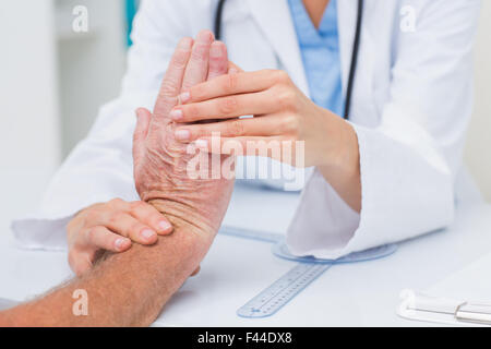 Physiotherapist examining male patients wrist - Stock Photo
