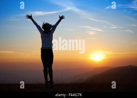 Silhouette of jumping young woman - Stock Photo