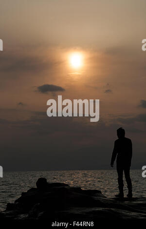 Silhouette of man on rocks overlooking the sea with the sun low in the sky behind cloud haze - Stock Photo