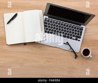 Laptop and opened Notepad on wooden table top view. - Stock Photo