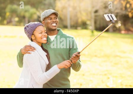 Young smiling couple taking selfies - Stock Photo