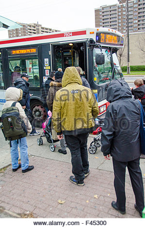 Passengers in winter clothes, standing in line to board a TTC bus. The bus has '24 Victoria Pk Stn' written on it. - Stock Photo