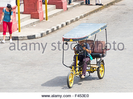 Transportation in Cuba. Person pedaling a rickshaw on a street in Santa Clara, Cuba. Two other seats in the rickshaw - Stock Photo