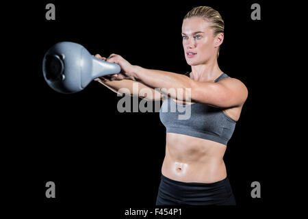Muscular woman swinging heavy kettlebell - Stock Photo