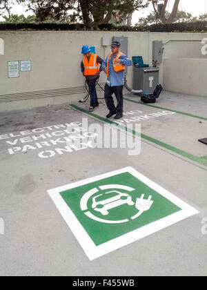 Repair technicians maintain an electric car charging station at an Irvine, CA, hospital parking lot. Note symbolic - Stock Photo