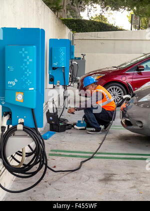 Repair technician maintains an electric car charging station at an Irvine, CA, hospital parking lot. Note electric - Stock Photo