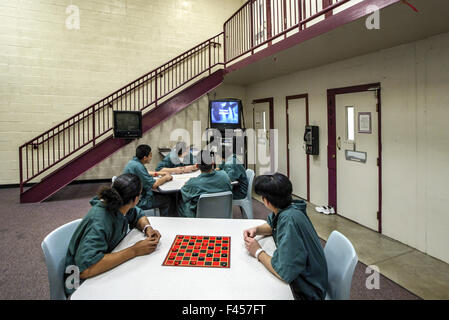 Uniformed Hispanic teenage inmates of an Orange, CA, juvenile prison play checkers in their day room. Note television. - Stock Photo