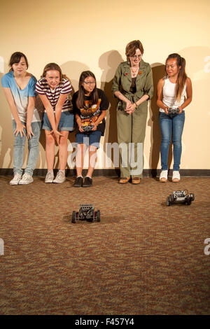Excited multiracial preteens and a librarian watch a 'Robot Challenge Night' race at a public library multipurpose - Stock Photo