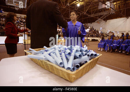 A Hispanic middle school girl wearing a blue graduation gown receives her diploma with a handshake from the school - Stock Photo