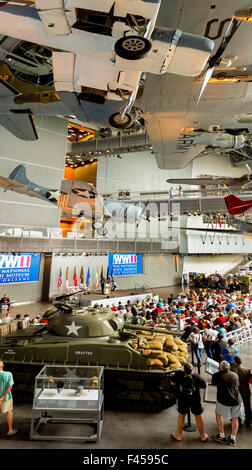 Surrounded by historical weapons, a crowd gathers for a Memorial Day observance at the Nation World War II Museum - Stock Photo