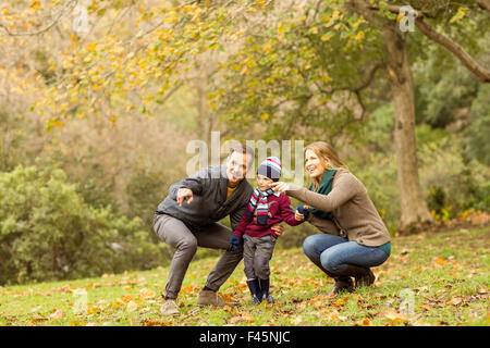 Young couple pointing something to their little boy - Stock Photo