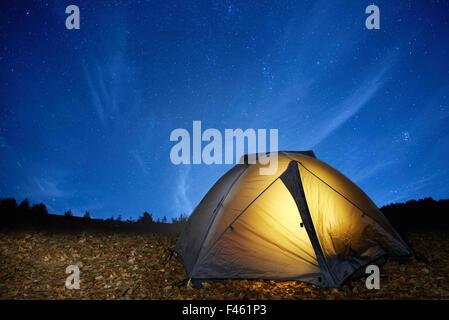 Illuminated yellow camping tent - Stock Photo