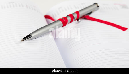 pen on notebook with red string - Stock Photo