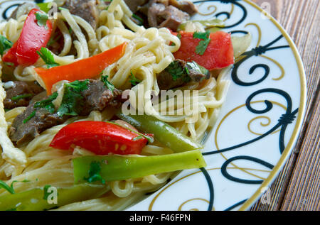 Kaurma laghman noodles. fried lamb and omelette. Central Asian cuisine - Stock Photo