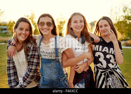Group of teenage girls hanging out in a park on a summer day - Stock Photo