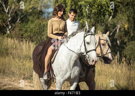 Young couple in love riding a horse Stock Photo