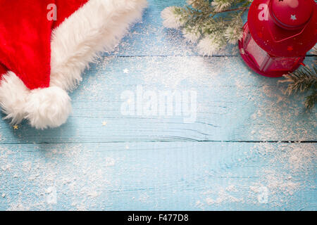 Santa Claus hat and lantern on blue snowy boards abstract concept - Stock Photo