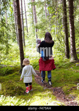 A woman with two children in the forest, Sweden. - Stock Photo