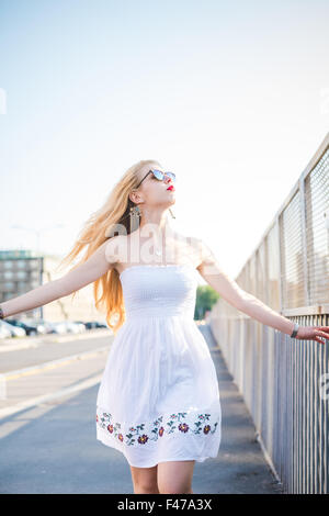 Knee figure of young handsome caucasian long blonde straight hair woman walking in the city, overlooking left, feeling - Stock Photo