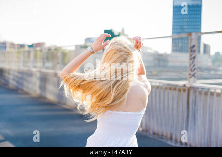 young handsome caucasian long blonde straight hair woman dancing in the city, view from back, feeling free in the - Stock Photo