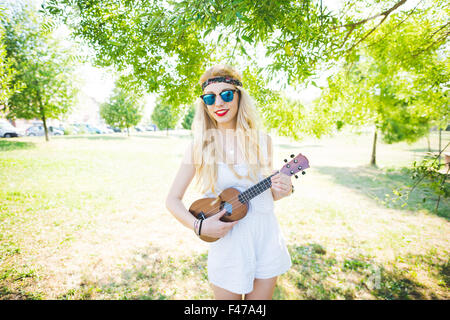Knee figure of young handsome caucasian long blonde straight hair hippy woman posing in a city park, playing a ukulele, - Stock Photo