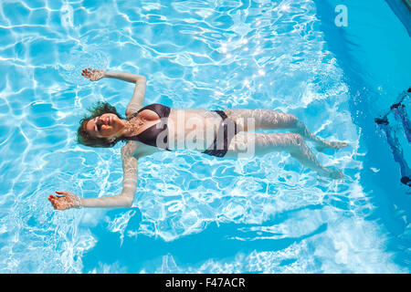 Pregnant woman floating in pool stock photo royalty free image 38714457 alamy for Girl pregnant in swimming pool