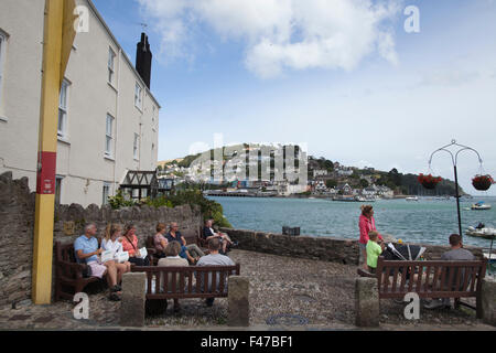 People eating fish & chips on Bayard's Cove looking out towards Kingswear across the River Dart, Dartmouth, Devon, - Stock Photo