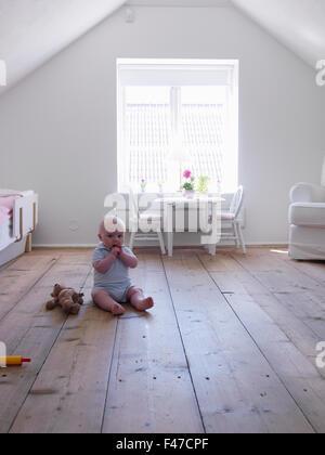 Baby girl sitting on wooden floor, Sweden. - Stock Photo