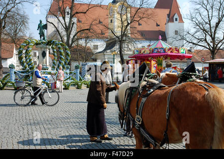 Man dressed in traditional Bavarian clothing offering tours in a horse drawn cart at the Easter fair on Paradeplatz, - Stock Photo