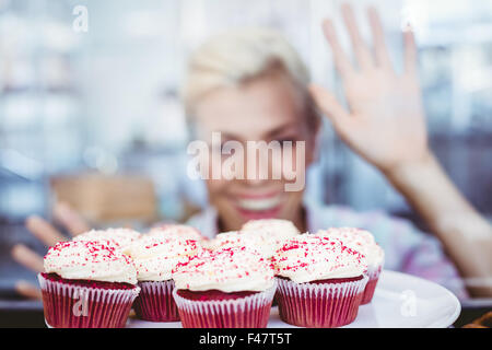 astonished pretty woman looking at cup cakes stock photo - Woman Decorating Cupcakes