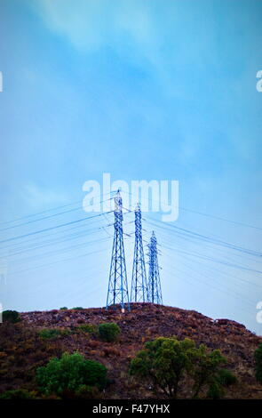 Electric power pylon and wires silhouetted by blue morning sky just before sunrise - Stock Photo