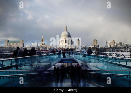 People walking across Millennium Bridge in London with St Paul's Cathedral in the background - Stock Photo