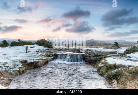 An idyllic winter scene with snow on the ground and a beautiful waterfall, on Dartmoor National Park in Devon - Stock Photo