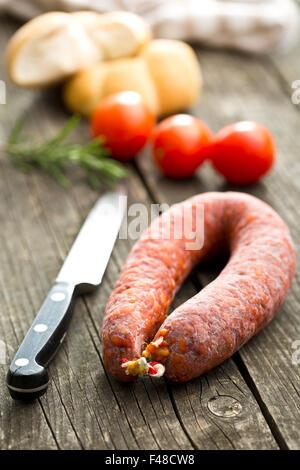 Chorizo sausage on old wooden table - Stock Photo