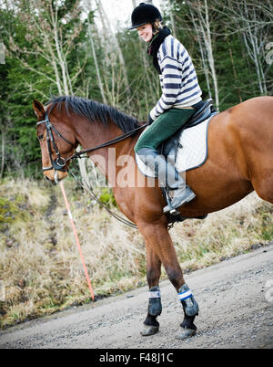 Young woman riding a horse, Sweden. - Stock Photo