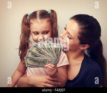 Happy casual family holding dollars and thinking how to spend the money. Vintage portrait - Stock Photo