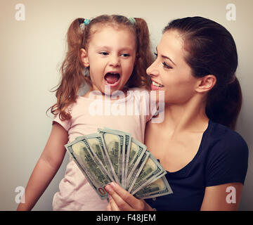Happy smiling family holding dollars and thinking how to spend the money. Vintage closeup portrait - Stock Photo