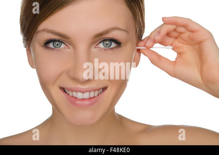 smiling woman cleans ears with cotton sticks - Stock Photo