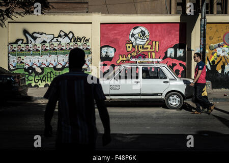 Minya, Egypt. 15th Oct, 2015. Egyptians walk by a wall where posters of candidates for the upcoming parliamentary - Stock Photo