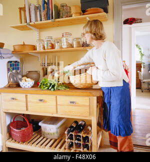 Woman in a rustic kitchen, Sweden. - Stock Photo