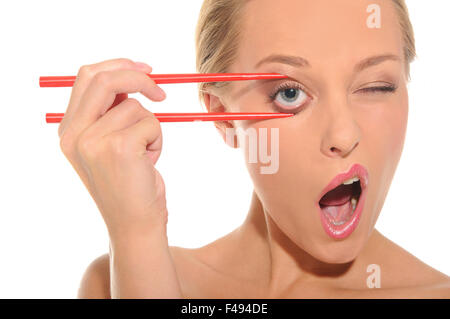 Surprised woman opens her eyes chopsticks - Stock Photo