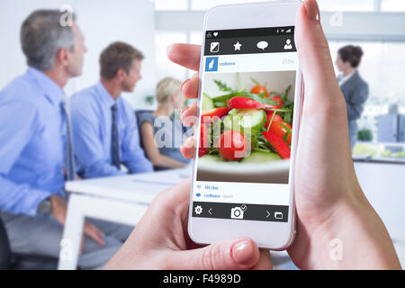 Composite image of hand holding smartphone - Stock Photo