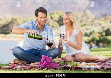 Cute couple on date pouring red wine - Stock Photo
